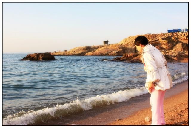 在金色阳光下的海滩玩耍的女儿